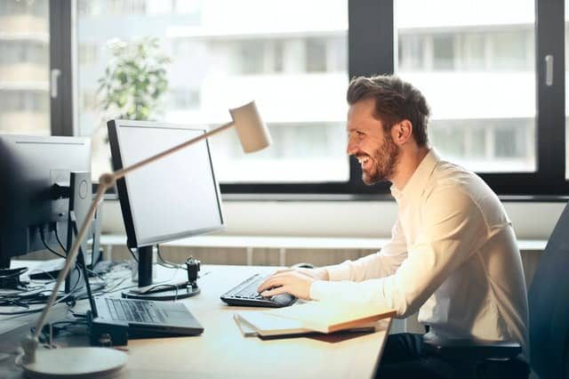 a person smiling and looking at his computer