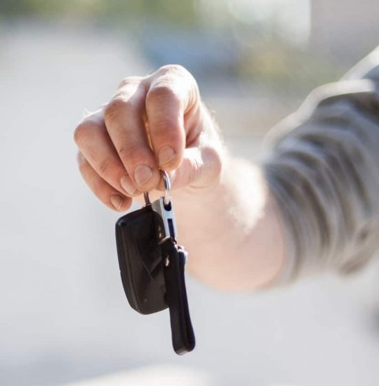 a person holding new car keys